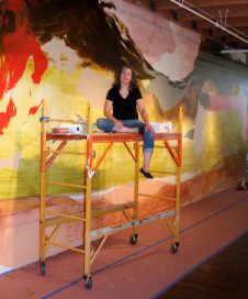 "Kim Piotrowski, taking a break while painting ""Tide Tango"" acrylic ink, acrylic and latex on wall, 43' x 13.'"