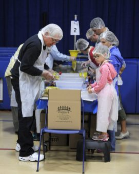 Ron Aulerick and Caroline Moran, 7, help bag macaroni at the Village Commons in North Riverside for Feed Our Community Day Saturday. Volunteers gathered to pack meals for needy families. (Photo by Jennifer Wolfe)