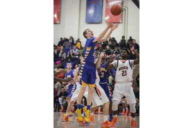 LTHS sophomore forward Connor Niego pulls down a rebound during the Lions' 60-51 win over host OPRF on Friday, December 20, 2014. (Chandler West/Staff Photographer)