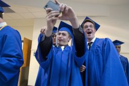 Andrew Misiorowski (center) instructs his friends, including Zachary Mullaney to gather for a selfie before the graduation ceremony at Riverside-Brookfield High School on May 23.