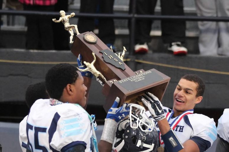 Dimitri Joe (left #55 slightly back to camera) and Kevin Jackson hoist the IHSA Class 6A state championship trophy after Nazareth's 26-7 victory over Lemont in Champaign. (Courtesy Alena Murguia)