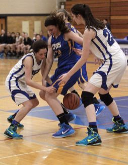 Miranda Chavez, left, and Dana Rettke, right, apply pressure to an LTHS player. (Photo by Kevin Tanaka)