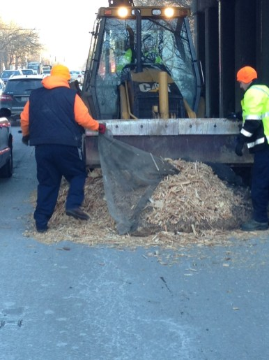 Riverside Public Works employees remove wood chips from northbound First Avenue on Thursday morning. The wood chip bundle apparently fell off the back of a truck while going under the railroad viaduct. (Photo courtesy of the Riverside Police Department)