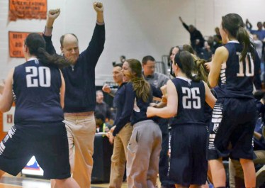 As the Blazers recover a rebound with one second left in the game, Head Coach Eddie Stritzel celebrates with his arms in the air. The team storms the court as the Trinity Blazers defeat rival Whitney Young High School. (Curtis Schuelke)