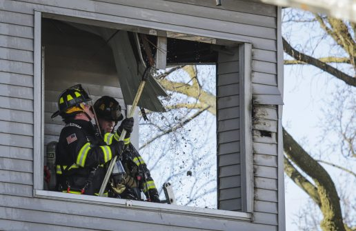 Firefighters pull down siding from the front porch area of the residence at 9129 Washington Ave.
