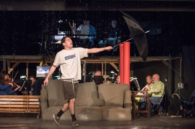 Gerald Kelel, who plays Don Lockwood in the North Riverside Players' Singin' in the Rain, gives the rain machine a workout during a rehearsal Monday at the Village Commons. | Max Herman/Contributing Photographer