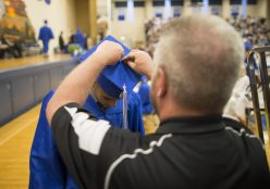 A staff member helps a graduating senior of class 2015 adjust his tassel on his cap. | Ting Shen/Contributor
