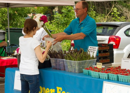 Nicole Knapp, left, buys flowers at the Cooper Farms stand at the Brookfield farmers market on Saturday, June 13, 2015. |Photo by Jennifer T. Lacey