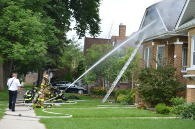 Firefighters shoot water into the top floor windows of the bungalow at 3308 Sunnyside Avenue, damaged by a fire on the afternoon of June 25. (Photo by Code Photography)