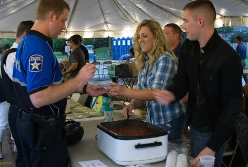 Jennifer Gallion grabs a sample of the North Riverside Police Department's entry during the North Riverside Autumn Fest and Chili Cook-Off on Sept. 18. | JENNIFER T. LACEY/Contributor