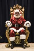 Santa Claus sits on stage in a gold-coated royal chair as he waits for children to tell him what they want for Christmas during Breakfast with Santa in North Riverside, Dec. 20. | Arturo Hidalgo/Contributor