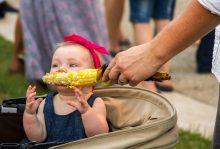 Winleigh Moore eats her first corn on the cob at Riverfest in the Park on Saturday, July 25. | Jennifer T. Lacey/Contributor