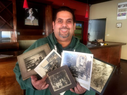 Zeze Aiyash holds up several of the roughly 20 historic photos of Brookfield that he and his business partner found in the basement of the former Fisher's Pharmacy. | BOB UPHUES/Staff
