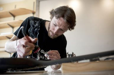 Justin Atwood performs some repair work on a guitar at his shop on Broadway Avenue in Brookfield. In addition to repairs, Atwood is building a pair of prototypes for guitars he'd like to produce. | William Camargo/Staff Photographer