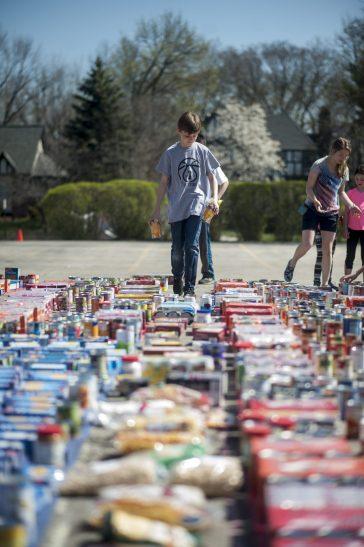 William Carl helps arrange the massive amount of food during Hauser Junior High School food drive. | William Camargo/Staff Photographer