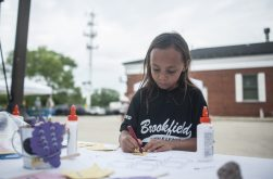 Mia Lopez makes some arts and crafts during the opening day of the Brookfield Farmers Market. | William Camargo/Staff Photographer