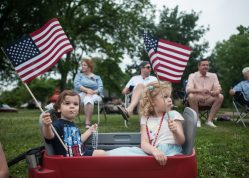 Luca and Annalisa Sandorff enjoy some lollipops and other swag as they wave their American flags at those marching down Longcommon Road during the Riverside Fourth of July parade on Monday. | WILLIAM CAMARGO/Staff Photographer