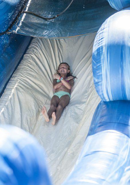 Sofia Senese zips down a water slide set up outside the Riverside Swim Club. | William Camargo/Staff Photographer