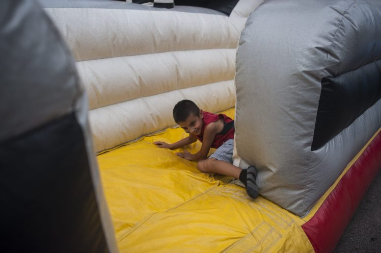 Max Perez comes tumbling down a inflatable slide during RiverFest in downtown Riverside on July 23. | William Camargo/Staff Photographer