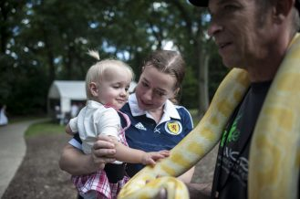 Lorna Reid holds her daughter Teagan and pets a snake during the 100th Annual Scottish Home Picnic in North Riverside on Aug. 6.   William Camargo/Staff Photographer