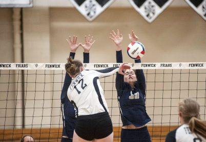 Fenwick outside hitter Margaret Planek spikes a ball against a pair of Trinity defenders. The Friars defeated the visiting Blazers 25-18, 19-25, 25-16 in a match earlier this season. (William Camargo/Staff Photographer)