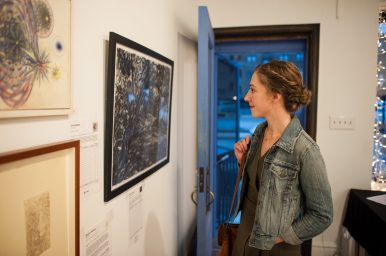 Elizabeth Lalley looks at some of the artwork during RAC The House art gala at the Riverside Arts Center on Oct. 1 in downtown Riverside. | William Camargo/Staff Photographer