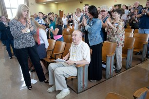 Joseph Lis receives one of several standing ovations from family, community leaders and former students during a dedication ceremony at S.E. Gross Middle School in 2013. | File 2013
