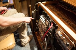 Organ tuner Martin Hill shows the electronic add ons to the organ. | William Camargo/Staff Photographer
