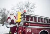 Santa on top of a North Riverside fire truck during his annual tour to meet the village's children. | William Camargo/Staff Photographer