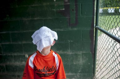 Miguel Melendez uses a wet towel to cool down in between innings during a Brookfield Little League game on June 18. | William Camargo/Staff Photographer