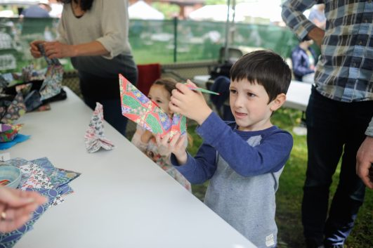 Nathan Schwartz makes a paper animal during the Riverside Arts Weekend event in Guthrie Park on May 21. | William Camargo/Staff Photographer