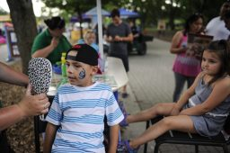 Andres Lopez looks at his finished face paint during Brookfield Zoo's Summer Nights concert on Friday, June 30. | William Camargo/Staff Photographer