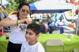 Marco Salcedo gets his hair painted by Ana Salcedo in a booth during the RiverFest in downtown Riverside on July 22.   William Camargo/Staff Photographer