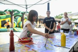 Zoe Bolchert contributes some brushstrokes for a community banner that the Riverside Arts Center had created as an activity at RiverFest in downtown Riverside on July 22.   William Camargo/Staff Photographer