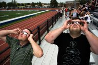 Mario Shermack, left, along with a fellow professor, view the solar eclipse at Riverside-Brookfield High School on Monday. | Sebastian Hidalgo/Contributor