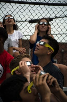 Riverside-Brookfield High School science students look up with solar glasses to view the eclipse on Monday at the football stadium. | Sebastian Hidalgo/Contributor