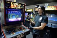 Doc Mack shows off the 1988 arcade classic Narc, the first video game he ever purchased. Mack's arcade, Galloping Ghost, now houses more than 600 games, lined up in tightly packed rows throughout multiple Ogden Avenue storefronts. The arcade will expand again soon, allowing it to hold about 800 games. | Alexa Rogals/Staff Photographer