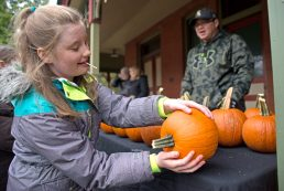 Amanda Santiago, 11, of Chicago, picks up a free pumpkin on Oct. 28, during the Monsters on Main Street costume contest at Grossdale Station in Brookfield. The Village of Brookfield handed out free pumpkins and taffy apples to dressed up participants. | Alexa Rogals/Staff Photographer