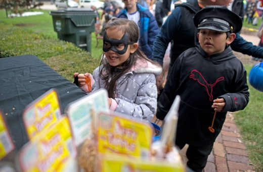 Children donned masks and costumes to grab a free taffy apple and pumpkins and take part in the costume contest at the Grossdale Station. | Alexa Rogals/Staff Photographer