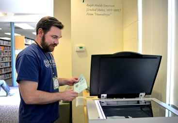 Frank Murray, the Brookfield Public Library's head of reference and electronic services, scans a document for the new digital record being created as part of the village's 125th anniversary celebration.   Alexa Rogals/Staff Photographer
