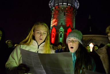 Hauser Junior High students Claire Schroeder and Elise Frank belt out a seasonal favorite accompanied by the school's seventh- and eighth-grade band during a Holiday Singalong in Centennial Park at the Riverside on Dec. 1. | ALEXA ROGALS/Staff Photographer