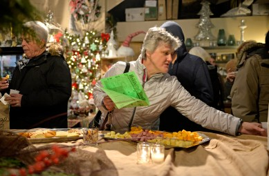 Attendees mingle and enjoy complimentary finger foods on Dec. 1, at Shamrock Garden Florist during the annual Riverside Chamber of Commerce Holiday Stroll throughout downtown Riverside. | ALEXA ROGALS/Staff Photographer
