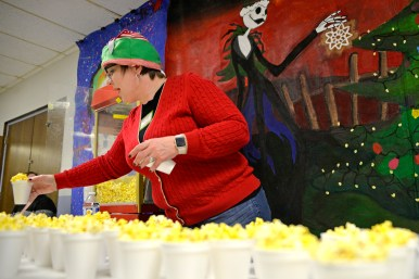 Shannon Heller, of Brookfield, serves cups of fresh popcorn at village hall on Dec. 2, during the annual Holiday Walk and celebration throughout Brookfield. | ALEXA ROGALS/Staff Photographer