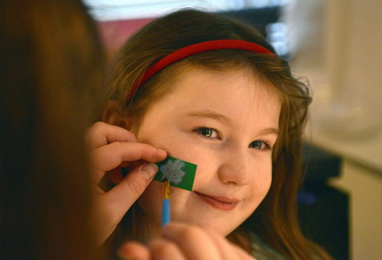 Audrey Swiderski, 4, of Riverside gets a shamrock painted on her face.   Alexa Rogals/Staff Photographer