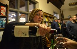 Stacey Cortez pours a splash of Beaujolais into the glass of one of the more than 300 people who paid 0 to attend Reading between the Wines, a wine-tasting fundraiser for the Riverside Public Library on Feb. 3. The money will be go toward a .3 million effort to renovate the lower-level Youth Services area. | Alexa Rogals/Staff Photographer