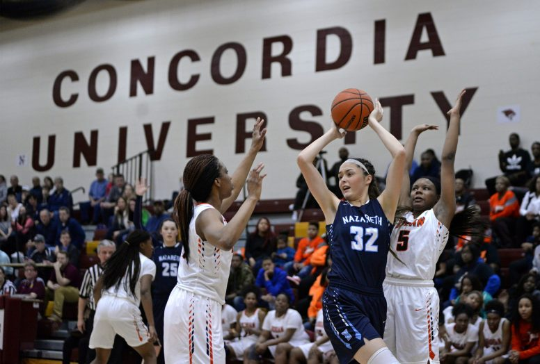Nazareth center Alyssa Geary looks to pass the ball under pressure from a couple of Bogan players during the Roadrunners' 68-47 win in the Class 3A Concordia University Supersectional on Feb. 26 (Alexa Rogals/Staff Photographer)