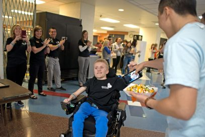 RBHS student Ethan Tkalec gets cheered on by other students and faculty as he enters on April 27, during lunch inside the cafeteria at Riverside Brookfield High School. | Alexa Rogals/Staff Photographer
