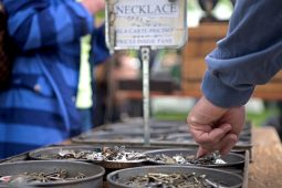 Attendees look through different jewelry pieces to make necklaces on May 19, during the annual Riverside Arts Weekend at Guthrie Park in Riverside. | Alexa Rogals/Staff Photographer
