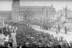 Troops of the 42nd Division in Baccarat, France, lead a May 28, 1918 funeral procession for more than 40 killed during a gas and artillery attack the previous day.   U.S. Army Signal Corps movie still, courtesy of National Archives