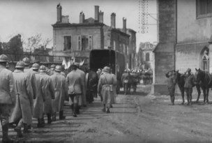French troops march behind trucks carrying coffins bearing American servicemen, including Rev. Hedley H. Cooper, during the funeral procession through Baccarat on May 27, 1918.   U.S. Army Signal Corps movie still, courtesy of National Archives